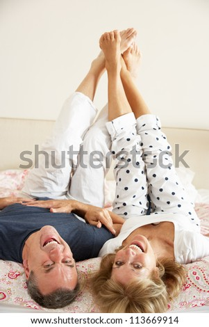 Senior Couple Lying Upside Down Together In Bed - stock photo
