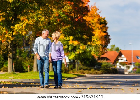 senior couple, Man and woman, having a walk in autumn or fall outdoors, the trees show colorful foliage - stock photo
