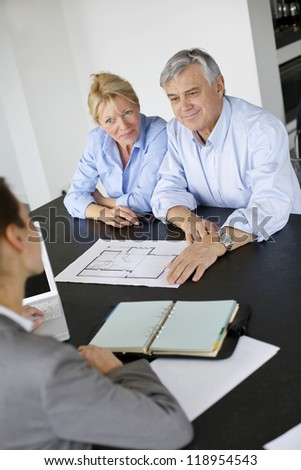 Senior couple meeting architect for building project