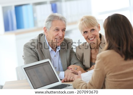 Senior couple meeting financial adviser in office - stock photo