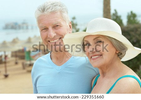 Senior couple near pool on the resort during vacation - stock photo