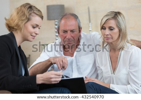 senior couple negotiating with businesswoman for new investment