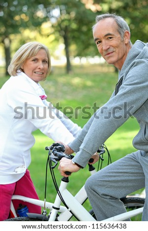 Senior couple on a bicycle - stock photo