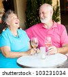 Senior couple on a date, laughing together over wine. - stock photo