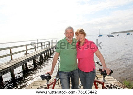 Senior couple on bicycle ride by a lakeside - stock photo