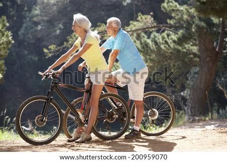 Senior couple on country bike ride - stock photo