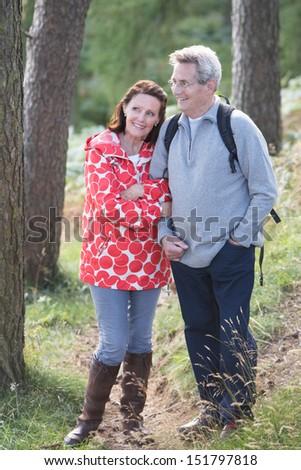 Senior Couple On Country Walk Through Woodland - stock photo