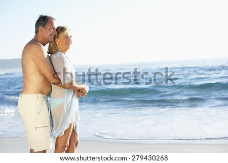 Senior Couple On Holiday Running Along Sandy Beach Looking Out To Sea