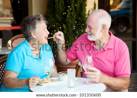 Senior couple on romantic lunch or dinner date.  He's feeding her the appetizer by hand. - stock photo