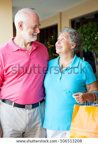 Senior couple on shopping trip look lovingly into each others eyes.