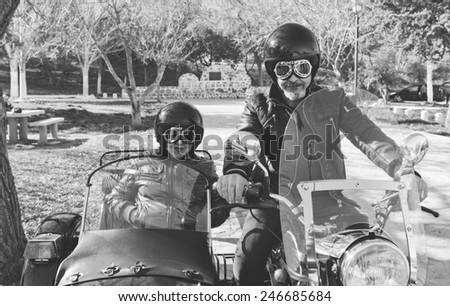 Senior couple on sidecar bike with monochrome effect - stock photo
