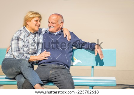 Senior couple on the bench - Two lovers relaxing and having fun while sitting on a bench - stock photo