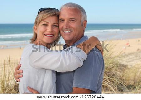 senior couple on vacation embracing - stock photo