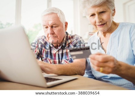 Senior couple paying bills online on laptop - stock photo