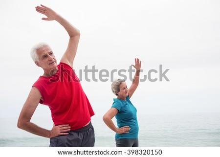 Senior couple performing stretching exercise on beach - stock photo