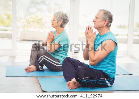 Senior couple performing yoga while sitting at home - stock photo