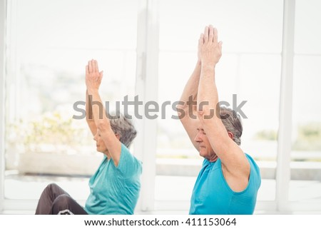 Senior couple performing yoga with arms raised at home - stock photo