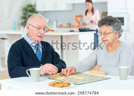 Senior couple playing a board game - stock photo