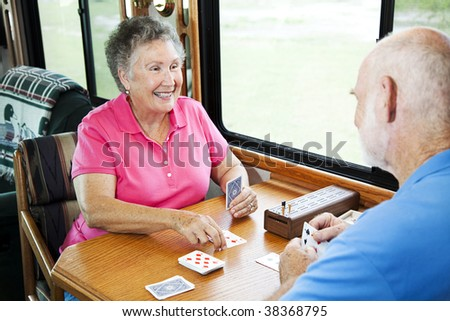 Senior couple playing a cribbage card game in their motor home.