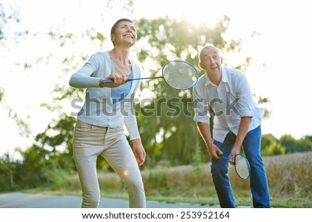 Senior couple playing badminton in summer in nature - stock photo