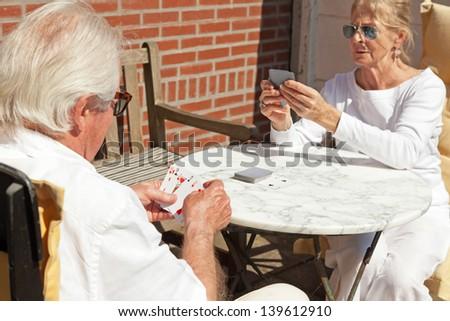 Senior couple playing card game outdoor in garden. - stock photo