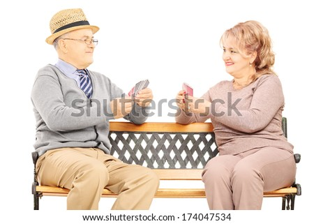 Senior couple playing cards seated on wooden bench isolated on white background - stock photo