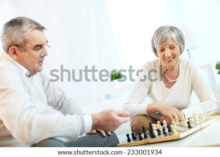 Senior couple playing chess - stock photo