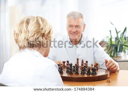 Senior couple playing chess at home.  - stock photo