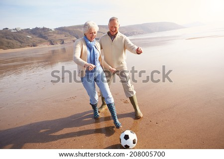 Senior Couple Playing Football On Winter Beach - stock photo
