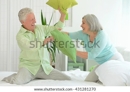 senior couple playing with pillows