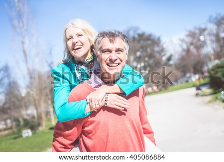 Senior couple portrait - Cheerful mature wife and husband walking outdoors and having fun - stock photo