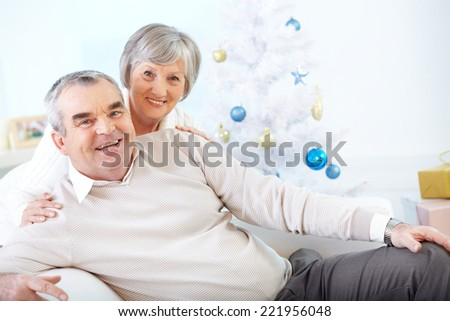 Senior couple posing at Christmas tree at home - stock photo
