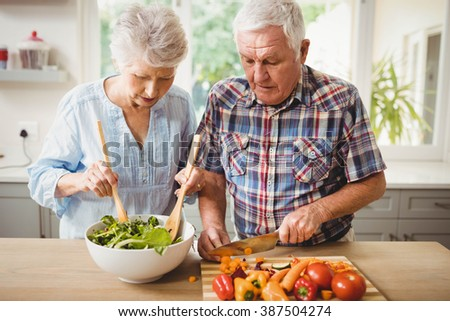 Senior couple preparing salad in kitchen - stock photo