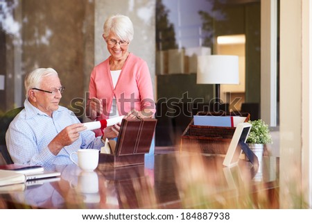 Senior Couple Putting Will Into Box - stock photo