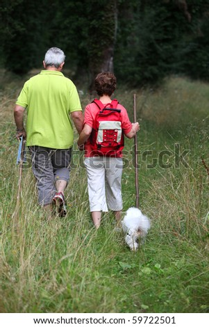 Senior couple rambling in country path with dog - stock photo