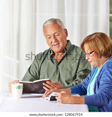 Senior couple reading books together in a rest home - stock photo