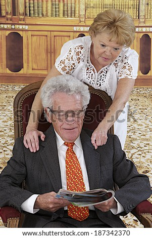 Senior couple reading magazine sitting on armchair  with reading room background  - stock photo