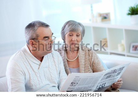 Senior couple reading newspaper together at home - stock photo