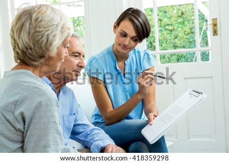 Senior couple reading report with female consultant at home - stock photo