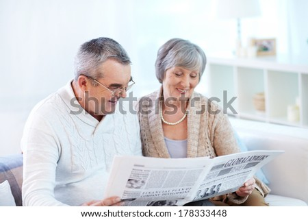 Senior couple reading together fresh newspaper - stock photo
