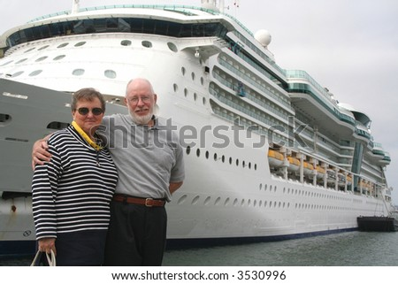 Senior couple ready for another cruise in front of a cruise ship. - stock photo