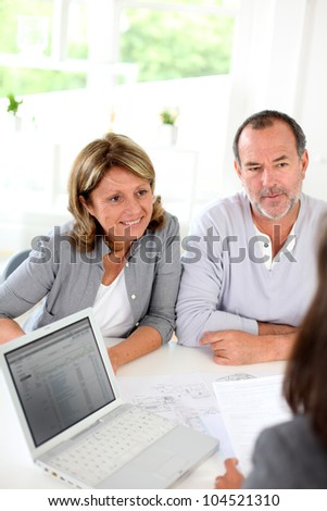 Senior couple ready to buy new house reading contract - stock photo