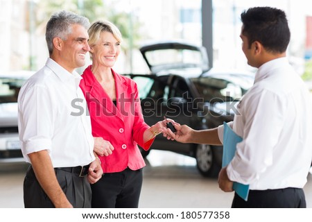 senior couple receiving car key after buying a new car - stock photo