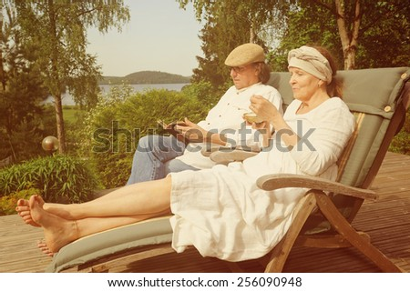 Senior couple relax in deckchairs on a wooden terrace, She is eating from a bowl and he is reading a book. Digital filters used to create a retro look. Lake and forest in the background. - stock photo