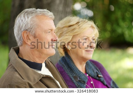 Senior couple relaxing at outdoors. Close-up portrait of smiling elderly woman and friendly old man sitting togetherness at park and relaxing.