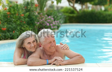 Senior couple relaxing at pool at hotel resort - stock photo