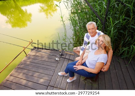 Senior couple relaxing at the lakeside. Smiling senior woman and man sitting on the pier and fishing.  - stock photo