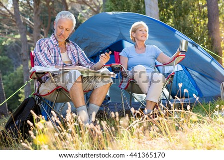 Senior couple relaxing beside their tent in the forest - stock photo