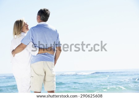 Senior Couple Relaxing By Ocean - stock photo