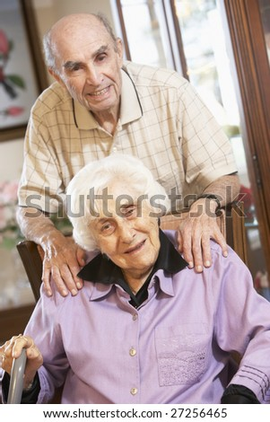 Senior couple relaxing in armchairs - stock photo